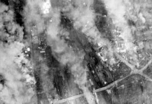 Vertical photographic-reconnaissance aerial taken over Dresden, Germany, following the two devastating attacks on the city by aircraft of Bomber Command on the night of 13/14 February 1945. A large number of fires still burn fiercely in the vicinity of the central goods depot and marshalling yards south of the River Elbe. C 4973 Part of AIR MINISTRY SECOND WORLD WAR OFFICIAL COLLECTION No. 542 Squadron RAF